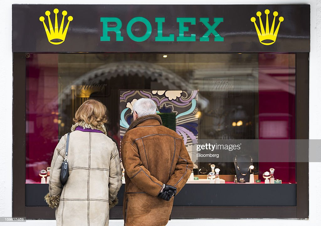 Pedestrians look at watches on display in the window of a store advertising Rolex in Gstaad, Switzerland, on Saturday, Jan. 19, 2013. Options traders are pushing the cost of bearish wagers on Swiss shares to the lowest level in almost seven years amid optimism a decline in the franc versus the euro will benefit the nation's exporters. Photographer: Valentin Flauraud/Bloomberg via Getty Images