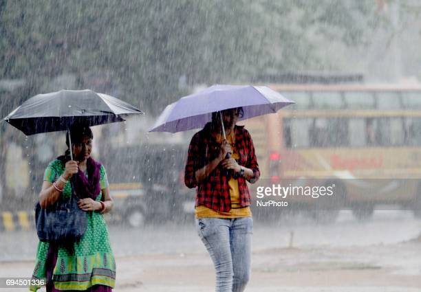 Pedestrians look on the road as they are protecting in the umbrella in the premonsoon time in the eastern Indian state Odisha's capital city...