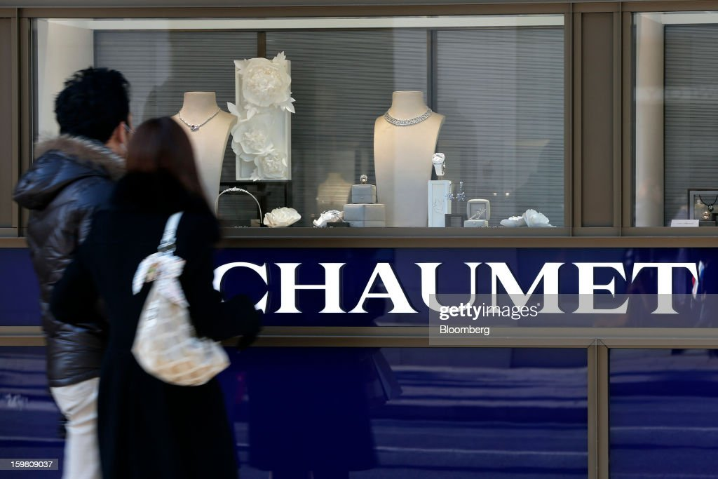 Pedestrians look through the window of a Chaumet store, a luxury unit of LVMH Moet Hennessy Louis Vuitton SA, in the Ginza district of Tokyo, Japan, on Sunday, Jan. 20, 2013. Japan's consumer prices excluding fresh food, a benchmark monitored by the central bank, haven't advanced 2 percent for any year since 1997, when a national sales tax was increased. Photographer: Kiyoshi Ota/Bloomberg via Getty Images