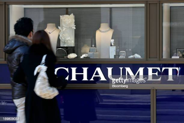 Pedestrians look through the window of a Chaumet store a luxury unit of LVMH Moet Hennessy Louis Vuitton SA in the Ginza district of Tokyo Japan on...