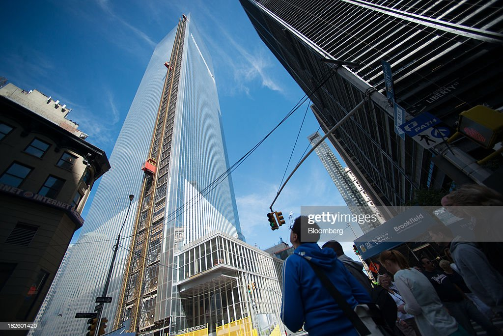 Pedestrians look up at the 4 World Trade Center building, managed by Silverstein Properties Inc., in New York, U.S., on Wednesday, Sept. 25, 2013. Real estate developer Larry Silverstein cant recoup any of the $1.2 billion recovered by World Trade Center insurers in settlements with airlines and airport security companies over the Sept. 11, 2001, terrorist attack that destroyed the office complex, a judge ruled. Photographer: Craig Warga/Bloomberg via Getty Images