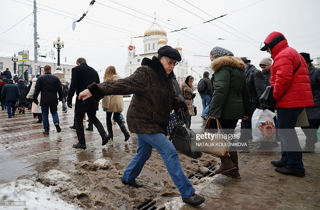 Pedestrians make their way across a puddle of melted snow near the Christ the Saviour Cathedral in central Moscow, on December 4, 2012. Moscovites woke up today to a thick blanket of snow covering the Russian capital.The temperatures in Moscow reached today 1C (34 F), but due to high humidity and wind, weather experts said it would feel more like - 3C (25 F).