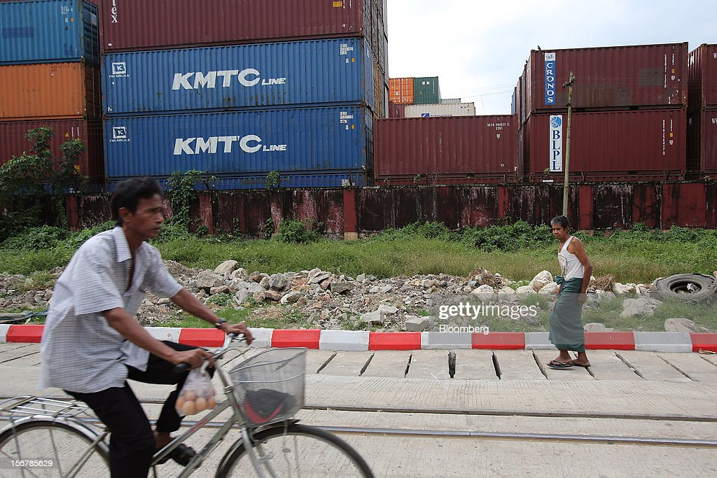 Pedestrians make their way past shipping containers stacked at a depot in Yangon, Myanmar, on Tuesday, Nov. 20, 2012. Myanmar's growth outlook has improved 'substantially' amid political reforms, which are expected to lead to a large influx of foreign investment, the Organization for Economic Cooperation and Development (OECD) said on Nov. 18. Photographer: Dario Pignatelli/Bloomberg via Getty Images