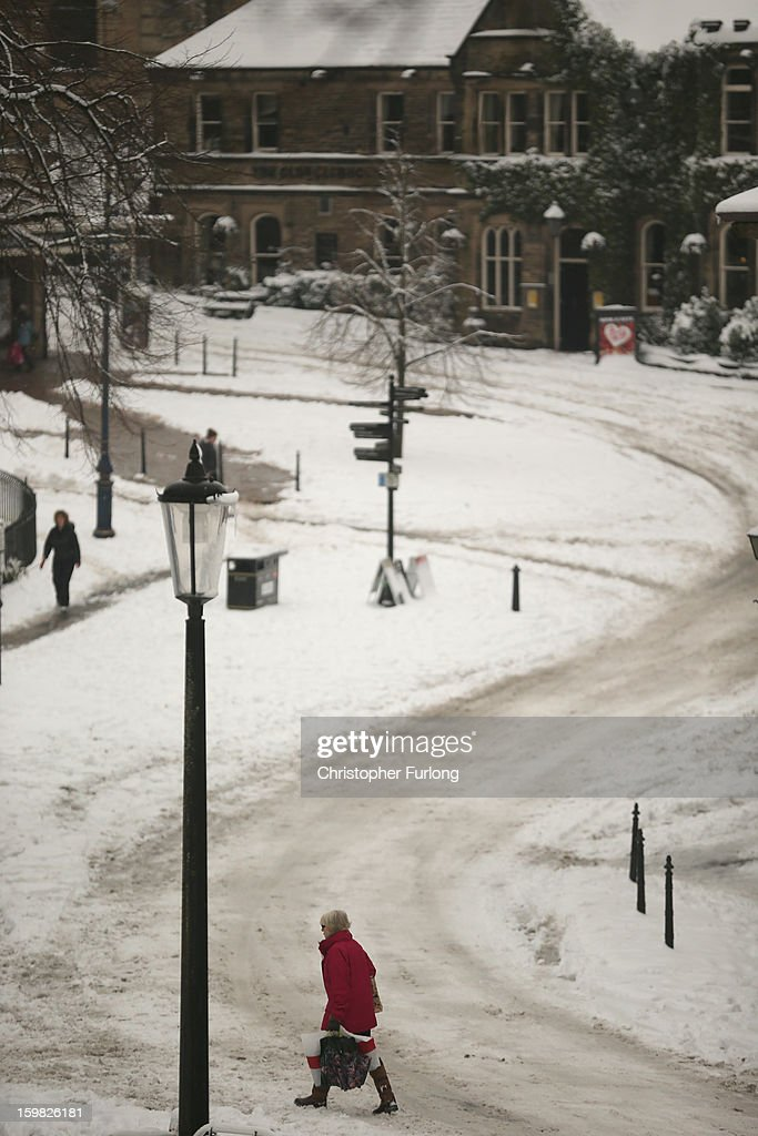 Pedestrians make their way through a snow covered Buxton on January 21, 2013 in Buxton, United Kingdom. The Met Office has issued a red weather warning for parts of the Uk and advising against all non-essential travel as up to 30cm of snow is expected to fall in some areas today. The adverse weather has closed nearly 5,000 schools and caused many airports to cancel flights.