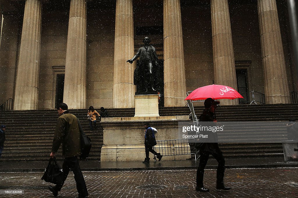 Pedestrians make their way through sleet and snow past the statue of George Washington in front of the Federal Hall on Wall Street during the morning commute on January 28, 2013 in New York City. Following some of the coldest weather this winter, temperatures are expected to gradually warm during the week in New York.