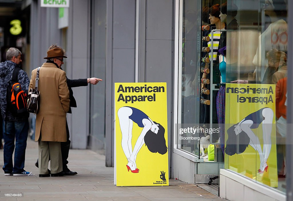 Pedestrians observe a window display outside an American Apparel Inc. store in Manchester, U.K., on Monday, April 1, 2013. U.K. retail sales unexpectedly stagnated in March in a sign that consumer spending remains under pressure from higher energy bills and weak wage growth. Photographer: Paul Thomas/Bloomberg via Getty Images
