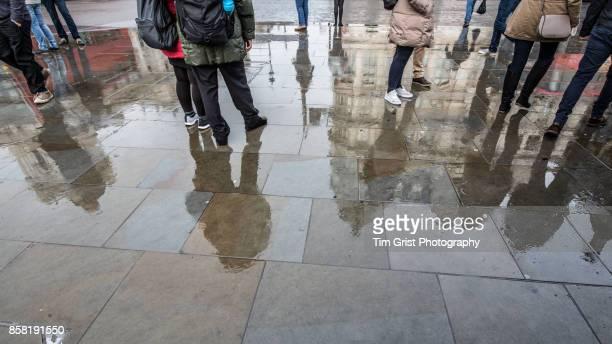 Pedestrians on a Wet Pavement London