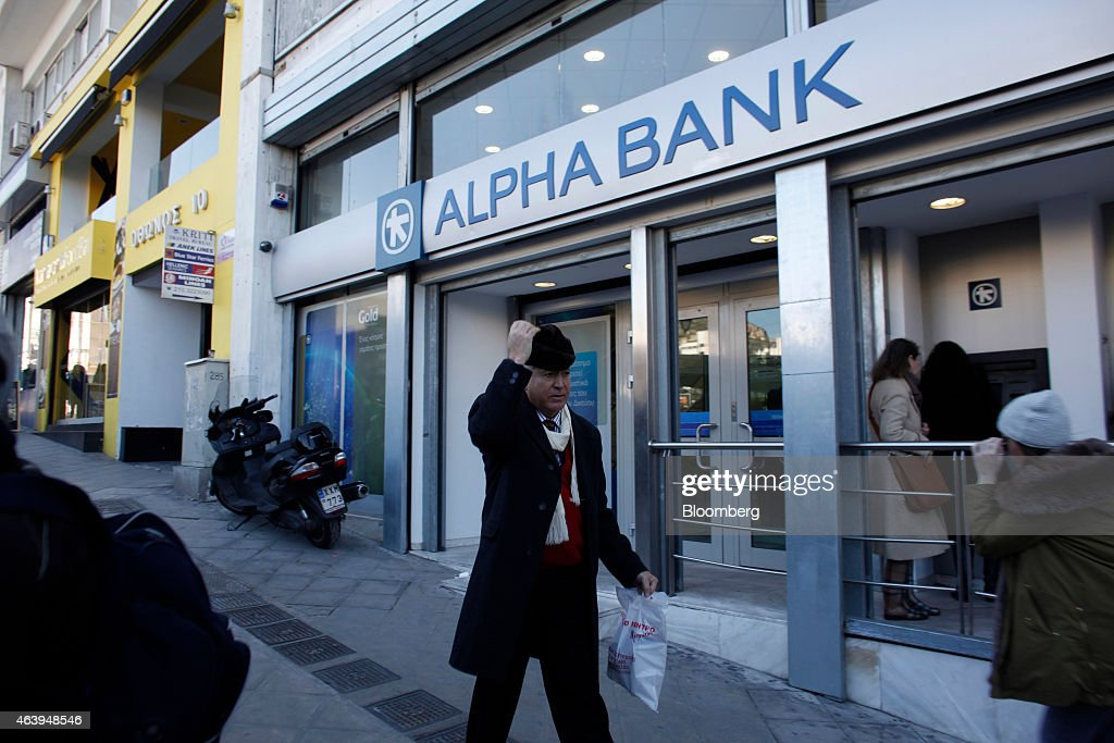 Pedestrians pass a Alpha Bank AE bank branch in Athens, Greece, on ...