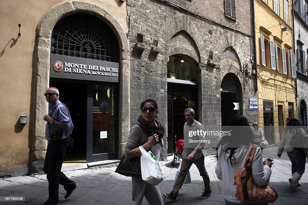 Pedestrians pass a Banca Monte dei Paschi di Siena SpA bank branch in Siena, Italy, on Monday, April 29, 2013. An Italian judge rejected a request by prosecutors to seize as much as 1.95 billion euros ($2.5 billion) of assets held by Nomura Holdings Inc. as they probed how Banca Monte dei Paschi di Siena SpA used derivatives to conceal losses. Photographer: Alessia Pierdomenico/Bloomberg via Getty Images