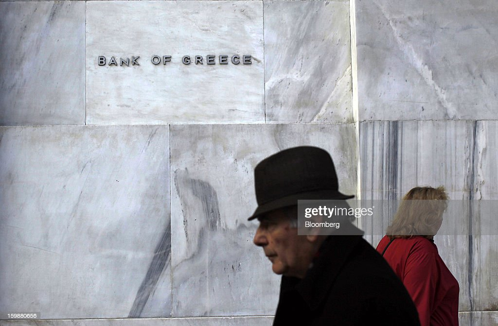 Pedestrians pass a Bank of Greece sign outside the headquarters of Greece's central bank in Athens, Greece, on Tuesday, Jan. 22, 2013. Euro-area finance ministers blessed the next disbursement of emergency aid for Greece, highlighting the goodwill that led to the unblocking of loans last month for Prime Minister Antonis Samaras's government. Photographer: Kostas Tsironis/Bloomberg via Getty Images