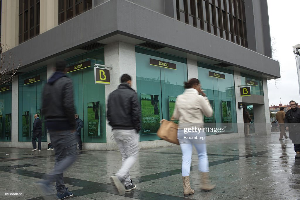 Pedestrians pass a Bankia SA bank branch in Madrid, Spain, on Thursday, Feb. 28, 2013. BFA-Bankia Chairman Jose Ignacio Goirigolzarri said a balance sheet clean-up that inflicted a 21.2 billion-euro ($27.6 billion) after-tax loss last year will set the Spanish banking group on course to repay state aid. Photographer: Angel Navarrete/Bloomberg via Getty Images
