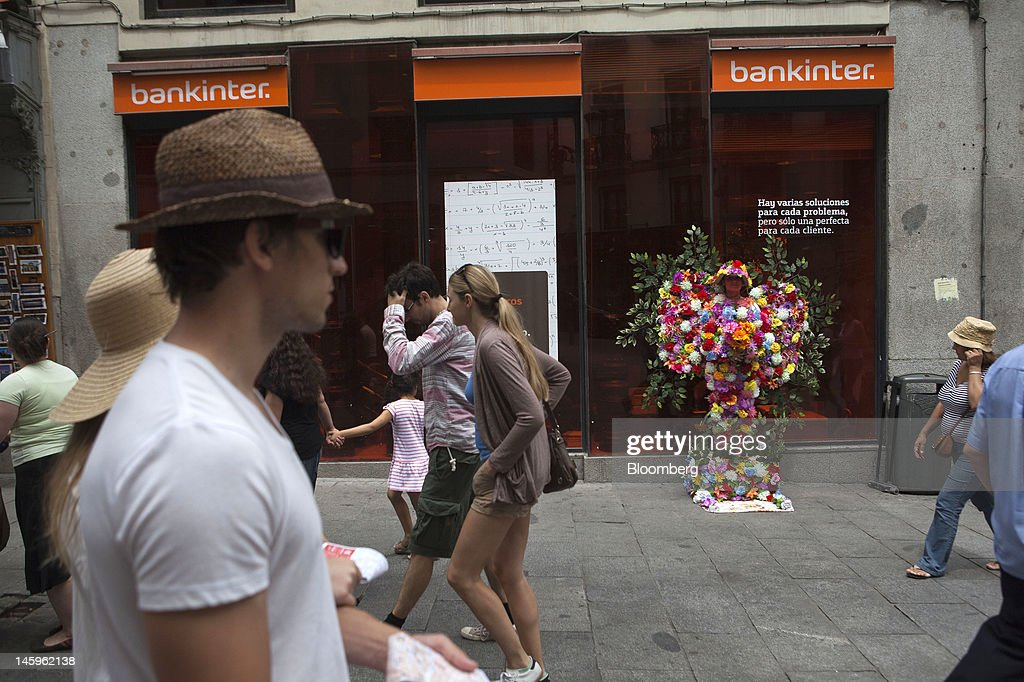 Pedestrians pass a Bankinter SA bank branch in Madrid, Spain, on Friday, June 8, 2012. Spain is poised to become the fourth of the 17 euro-area countries to require emergency assistance as the currency bloc's finance chiefs plan weekend talks on a potential aid request to shore up the nation's lenders. Photographer: Angel Navarrete/Bloomberg via Getty Images