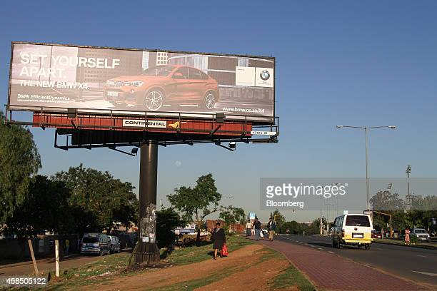 Pedestrians pass a billboard advertising the latest BMW AG X4 automobile for sale on a roadside in Soweto South Africa on Wednesday Nov 5 2014...