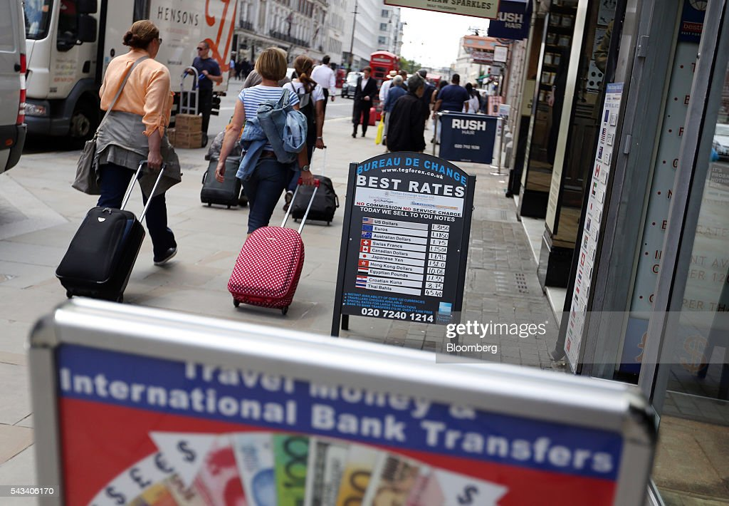 Pedestrians pass a board advertising exchange rates outside a foreign currency exchange bureau in London, U.K., on Tuesday, June 28, 2016. The pound rose for the first time since the U.K.s vote to leave the European Union, as a recovery in investor appetite for higher-yielding assets seeped through currency markets. Photographer: Chris Ratcliffe/Bloomberg via Getty Images