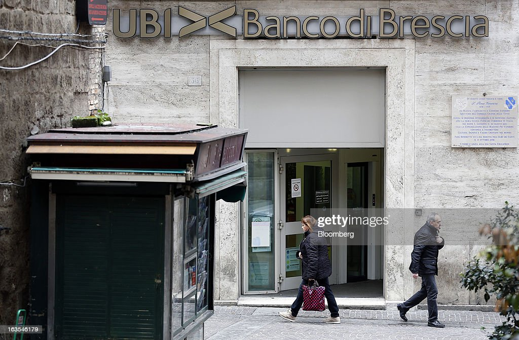 Pedestrians pass a branch of a Banco di Brescia bank branch, a subsidiary of Unione di Banche Italiane SCPA (UBI Banca), in Viterbo, Italy, on Monday, March 11, 2013. Intesa Sanpaolo SpA and UniCredit SpA are among Italian banks due to report losses for the fourth quarter this week, as the economic contraction meant more clients failed to repay their debts. Photographer: Alessia Pierdomenico/Bloomberg via Getty Images