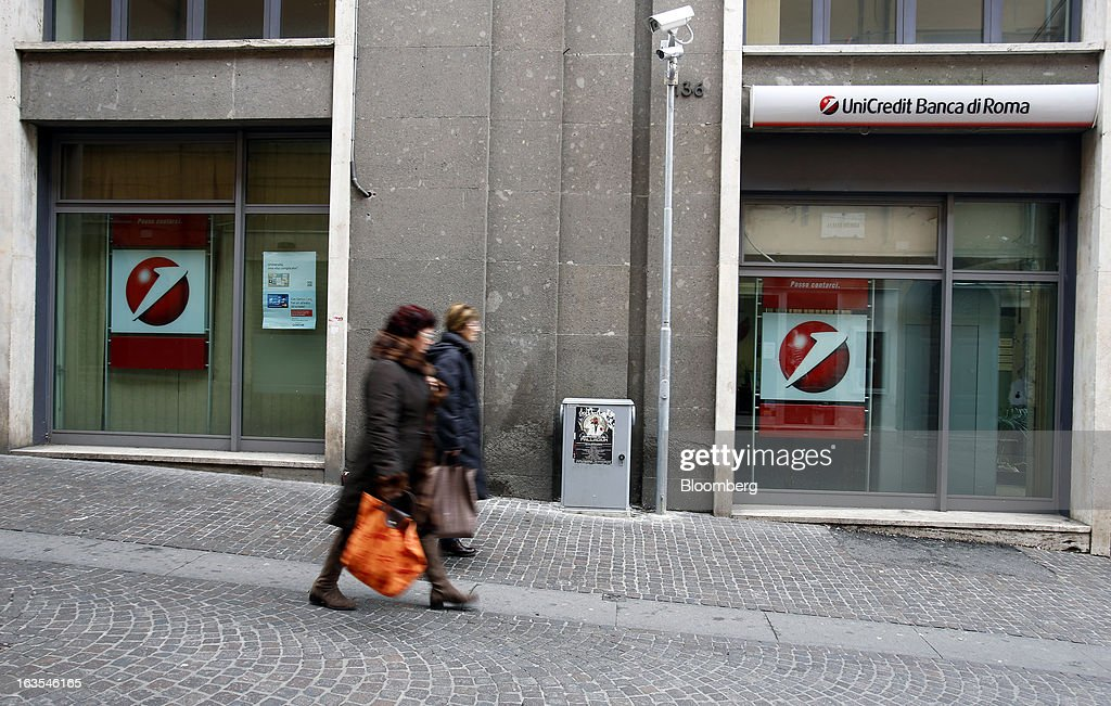 Pedestrians pass a branch of a UniCredit SpA bank in Viterbo, Italy, on Monday, March 11, 2013. Intesa Sanpaolo SpA and UniCredit SpA are among Italian banks due to report losses for the fourth quarter this week, as the economic contraction meant more clients failed to repay their debts. Photographer: Alessia Pierdomenico/Bloomberg via Getty Images