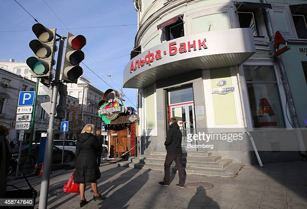 Pedestrians pass a branch of Alfa Bank in Moscow Russia on Monday Nov 10 2014 The ruble has lost more than 28 percent against the dollar so far this...