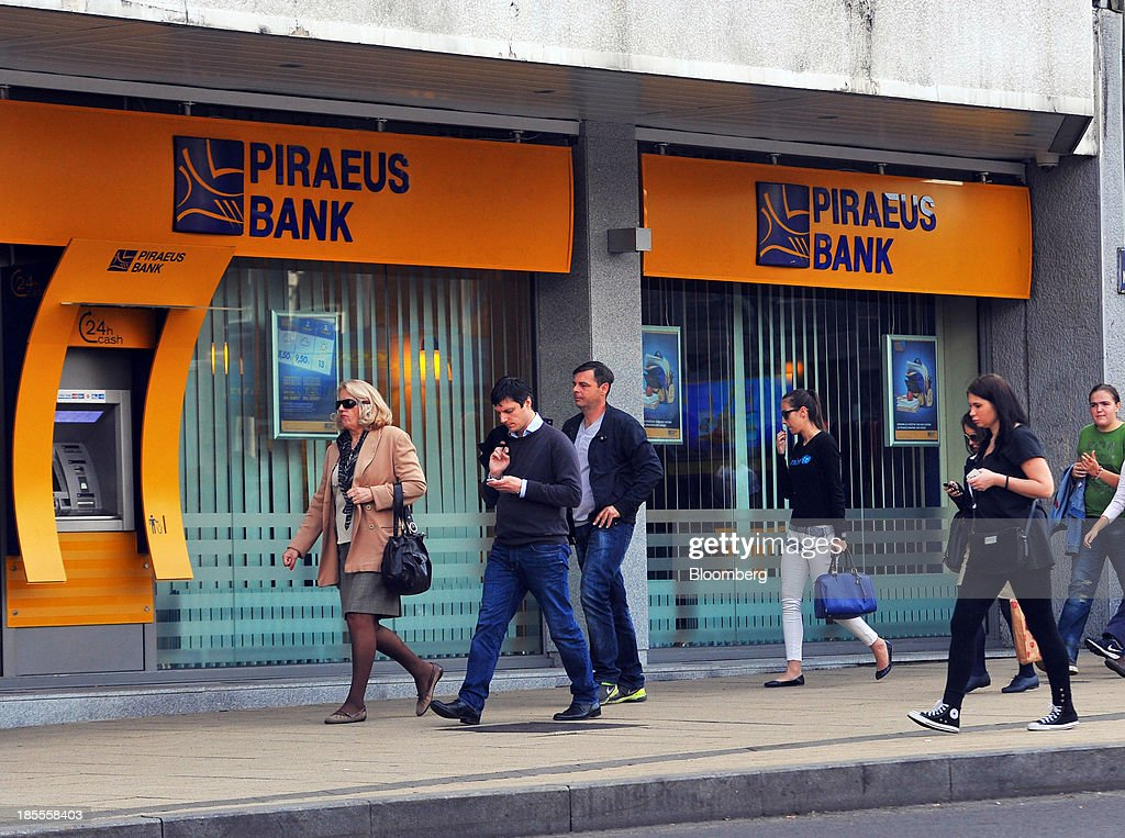 Pedestrians pass a branch of Piraeus Bank SA in Belgrade, Serbia, on Monday, Oct. 21, 2013. Serbia's government revealed a salvo of measures to bring the public finance deficit and debt back under control by 2017 after the head of the largest coalition party warned the country was on the brink of insolvency. Photographer: Oliver Bunic/Bloomberg via Getty Images