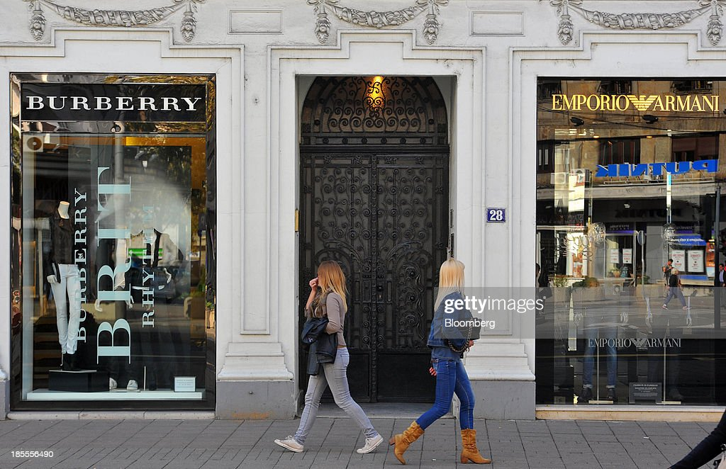 Pedestrians pass a Burberry Group Plc luxury store, left, and an Emporio Armani fashion clothing store, operated by Giorgio Armani SpA, in Belgrade, Serbia, on Monday, Oct. 21, 2013. Serbia's government revealed a salvo of measures to bring the public finance deficit and debt back under control by 2017 after the head of the largest coalition party warned the country was on the brink of insolvency. Photographer: Oliver Bunic/Bloomberg via Getty Images