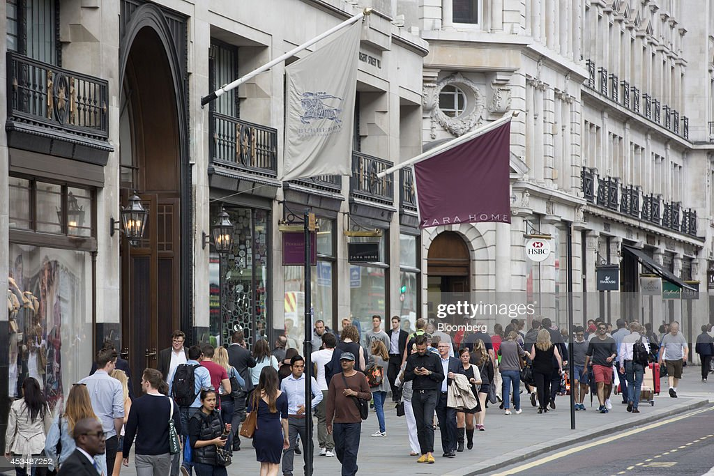 Pedestrians pass a Burberry Group Plc store left and a Zara Home store center as they pass buildings that form part of the Pollen Estate on Regent...