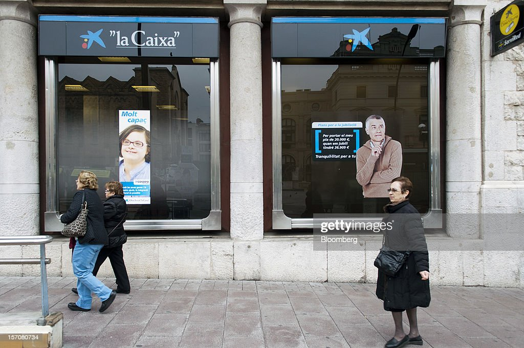 Pedestrians pass a CaixaBank SA branch in Sabadell, Spain, on Wednesday, Nov. 28, 2012. Spanish banks getting European aid will shrink their balance sheets more than 60 percent, the European Commission said, as BFA-Bankia, the biggest rescued lender, expects to lose 19 billion euros ($25 billion) this year. Photographer: Stefano Buonamici/Bloomberg via Getty Images