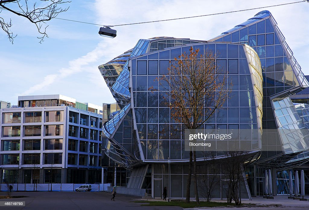 Pedestrians pass a campus building designed by Frank Gehry at Novartis AG's headquarters in Basel, Switzerland, on Wednesday, Jan. 29, 2014. Novartis AG, Europe's biggest drugmaker by sales, said fourth-quarter profit fell as currencies in emerging markets weakened against the dollar. Photographer: Gianluca Colla/Bloomberg via Getty Images
