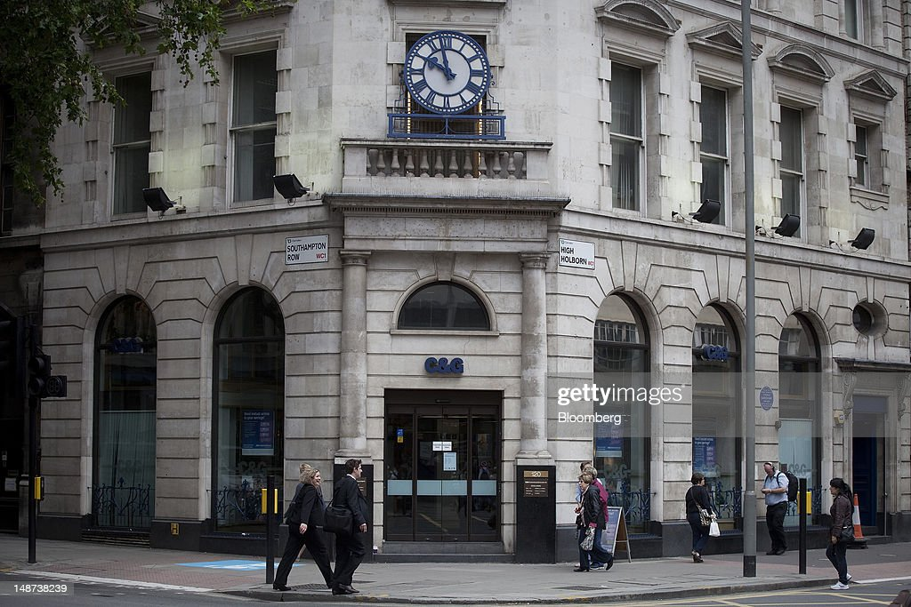 Pedestrians pass a Cheltenham & Gloucester bank branch, part of the Lloyds Banking Group Plc, in London, U.K., on Thursday, July 19, 2012. Lloyds Banking Group Plc agreed to sell 632 branches to Co-Operative Bank Plc for an initial 350 million pounds ($548 million), as the U.K.'s biggest mortgage lender divests assets to comply with its government bailout. Photographer: Simon Dawson/Bloomberg via Getty Images