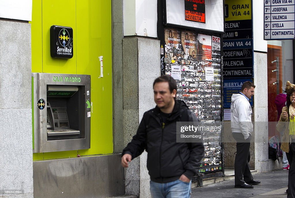 Pedestrians pass a closed-down retail store beside a Caja Madrid-branded automated teller machine (ATM) operated by Bankia SA in Madrid, Spain, on Wednesday, April 3, 2013. Prime Minister Mariano Rajoy told Spaniards they'll start to see the benefits of his reform program next year after he avoided becoming the fifth European leader to request a full sovereign rescue. Photographer: Angel Navarrete/Bloomberg via Getty Images