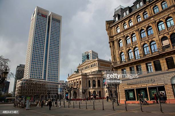 Pedestrians pass a Commerzbank AG bank branch as the UBS AG logo sits on the company's offices in Frankfurt Germany on Monday March 24 2014 German...