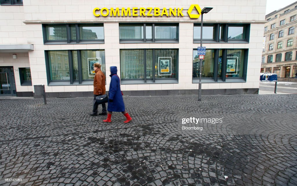 Pedestrians pass a Commerzbank AG bank branch in Frankfurt, Germany, on Friday, Feb.15, 2013. Commerzbank AG Chief Executive Officer Martin Blessing gave up his bonus for last year and cut the payouts by an average 17 percent across the firm, warning of higher costs and more pressure on revenue. Photographer: Ralph Orlowski/Bloomberg via Getty Images
