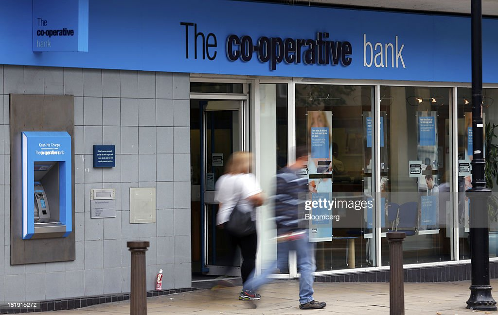 Pedestrians pass a Co-Operative Bank Plc branch, a unit of Co-Operative Group Ltd., in Bolton, U.K., on Wednesday, Sept. 25, 2013. The parent of Co-operative Bank Plc, which is seeking capital after losses, may avoid being forced to rescue the lender thanks to an accord it struck with regulators last year, according to bondholders. Photographer: Paul Thomas/Bloomberg via Getty Images