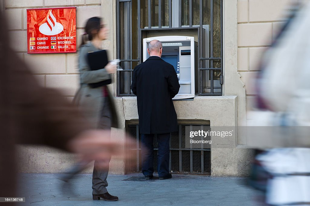 Pedestrians pass a customer standing at an automated teller machine (ATM) operated by Banco Santander SA in Barcelona, Spain, on Wednesday, March 20, 2013. Officials from the troika of international creditors -- the ECB, the International Monetary Fund and the European Commission -- are in Cyprus discussing further capital controls and possibly extending a bank holiday to the end of the week, a European official familiar with the talks said on condition of anonymity because the discussions are confidential. Photographer: David Ramos/Bloomberg via Getty Images