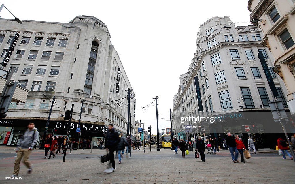 Pedestrians pass a Debenhams Plc department store, left, and a Primark store, operated by Associated British Foods Plc, right, in central Manchester, U.K., on Monday, April 1, 2013. U.K. retail sales unexpectedly stagnated in March in a sign that consumer spending remains under pressure from higher energy bills and weak wage growth. Photographer: Paul Thomas/Bloomberg via Getty Images