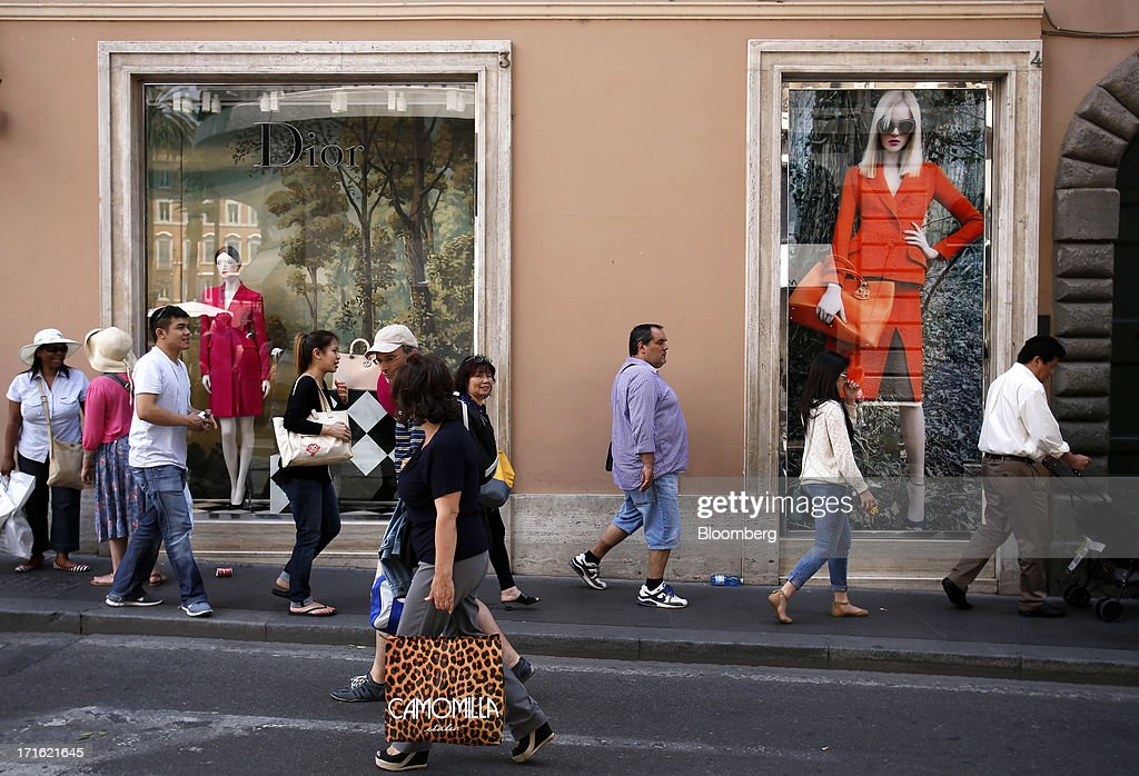 Pedestrians pass a Dior store, operated by Christian Dior SA, on Via Condotti in Rome, Italy, on Wednesday, June 26, 2013. Italian household confidence rose this month as consumers grew optimistic about the country's outlook as Prime Minister Enrico Letta's government plans to cut taxes and boost youth employment. Photographer: Alessia Pierdomenico/Bloomberg via Getty Images