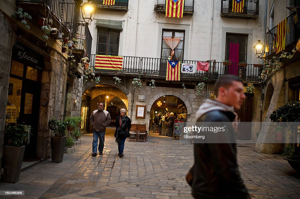 Pedestrians pass a display of pro-independence Catalan flags hanging from a building in Girona, Spain, on Thursday, Jan. 31, 2013. Spain's recession deepened more than economists forecast in the fourth quarter as the government's struggle to rein in the euro region's second-largest budget deficit weighed on domestic demand. Photographer: David Ramos/Bloomberg