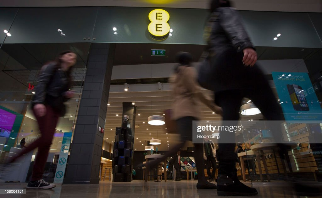 Pedestrians pass a EE (Everything Everywhere) store, a joint venture between France Telecom SA and Deutsche Telekom AG, in Stratford, U.K., on Monday, Dec. 5, 2012. France Telecom CEO Stephane Richard said in an interview last month that the Paris-based company has received interest from private-equity firms seeking a minority stake in the 50-50 venture, and may also consider an initial public offering of the unit. Photographer: Jason Alden/Bloomberg via Getty Images