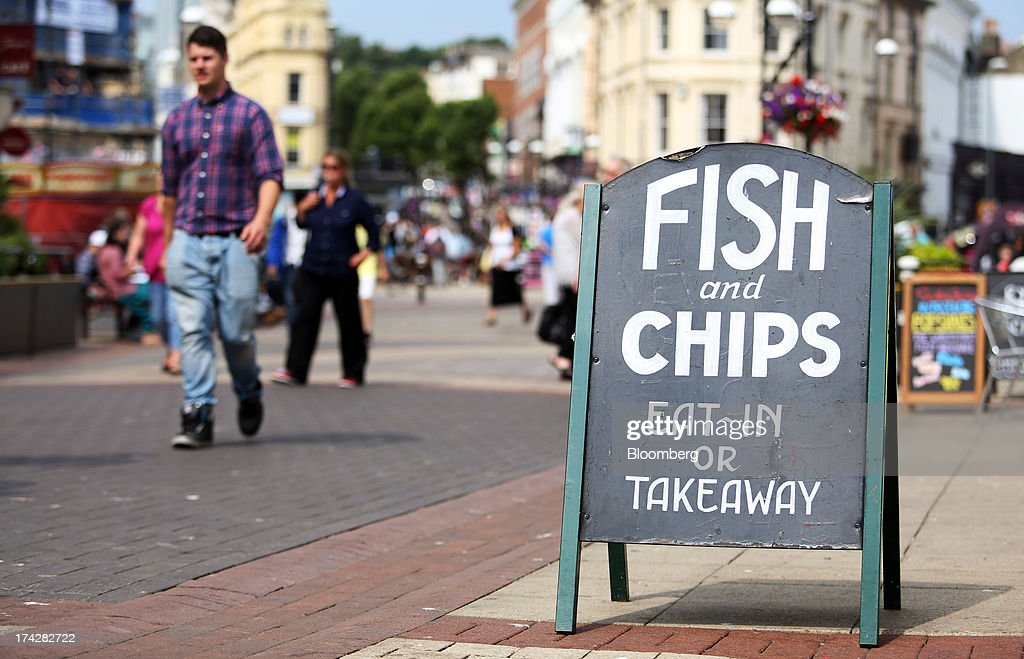 Pedestrians pass a fish and chips shop on the pedestrianised high street in Hastings, U.K., on Tuesday, July 23, 2013. U.K. retail sales rose for a second month in June as discounts at department stores drove demand for clothes and electrical products. Photographer: Chris Ratcliffe/Bloomberg via Getty Images