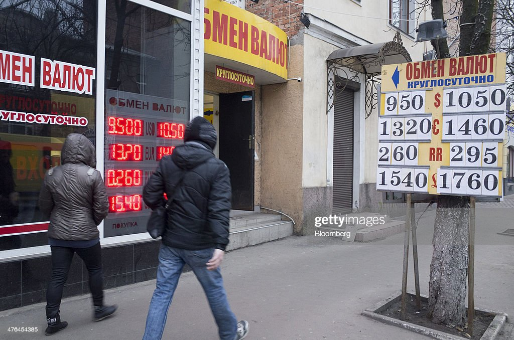 Pedestrians pass a foreign exchange office advertising ruble, dollar and euro currency for sale in Kharkiv, Ukraine, on March 2, 2014. Ukraine's Eurobonds slumped by the most on record as a Russian military incursion threatened efforts by the government in Kiev to obtain western economic aid and avert a debt default. Photographer: Vincent Mundy/Bloomberg via Getty Images