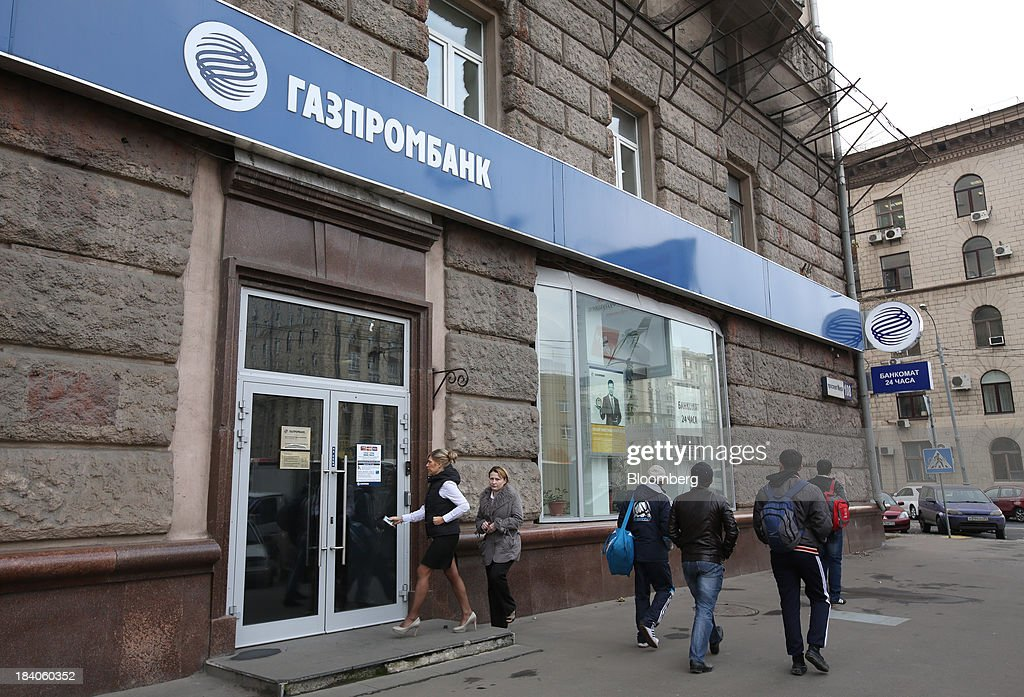 Pedestrians pass a Gazprombank OJSC bank branch in Moscow, Russia, on Friday, Oct. 11, 2013. Tinkoff Credit Systems is valued at $2.5b to $3b for London IPO, which reflects P/E multiple of 9.5 to 11.4, Vedomosti reports, citing unidentified people familiar with offering documents. Photographer: Andrey Rudakov/Bloomberg via Getty Images