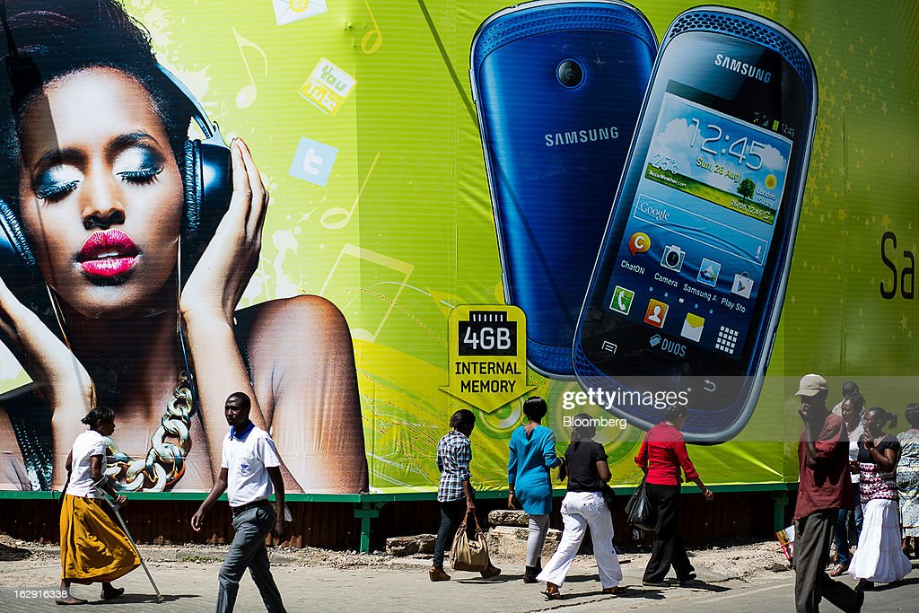 Pedestrians pass a giant advertisement for Samsung Electronics Co. mobile phones in Nairobi, Kenya, on Friday, March 1, 2013. Next week's presidential vote will be the first since disputed elections in 2007 triggered ethnic fighting in which more than 1,100 people died and another 350,000 fled their homes. Photographer: Trevor Snapp/Bloomberg via Getty Images
