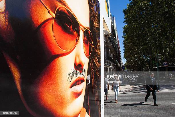 Pedestrians pass a graffiti damaged advertisement on a shopping street in Lisbon Portugal on Monday Sept 9 2013 Prime Minister Pedro Passos Coelho is...