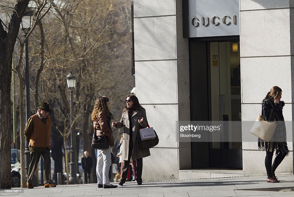 Pedestrians pass a Gucci store, a luxury unit of PPR SA, in Madrid, Spain, on Wednesday, Jan. 30, 2013. Spain's recession deepened more than economists forecast in the fourth quarter as the government's struggle to rein in the euro region's second-largest budget deficit weighed on domestic demand. Photographer: Angel Navarrete/Bloomberg via Getty Images