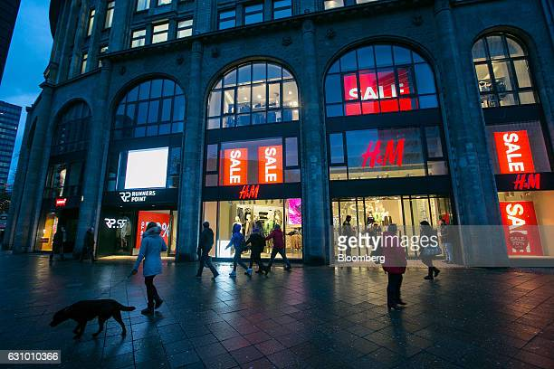 Pedestrians pass a Hennes Mauritz AB clothing fashion store as sales promotion signs sit on display in Berlin Germany on Wednesday Jan 4 2017 Germany...
