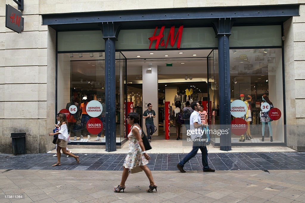 Pedestrians pass a Hennes & Mauritz AB (H&M) clothing store in Bordeaux, France, on Wednesday, July 17, 2013. Austerity measures and rising unemployment are restraining consumer spending in Europe, while retailers including Groupe Auchan SA and Casino Guichard-Perrachon SA are competing more aggressively on price. Photographer: Balint Porneczi/Bloomberg via Getty Images