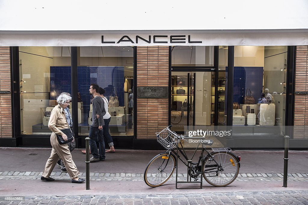 Pedestrians pass a Lancel luxury leather goods store in Toulouse, France, on Tuesday, Aug. 12, 2014. The euro traded 0.3 percent from a nine-month low before reports this week that may show growth in the region weakened and inflation slowed, adding to signs the bloc's economy is struggling to recover. Photographer: Balint Porneczi/Bloomberg via Getty Images