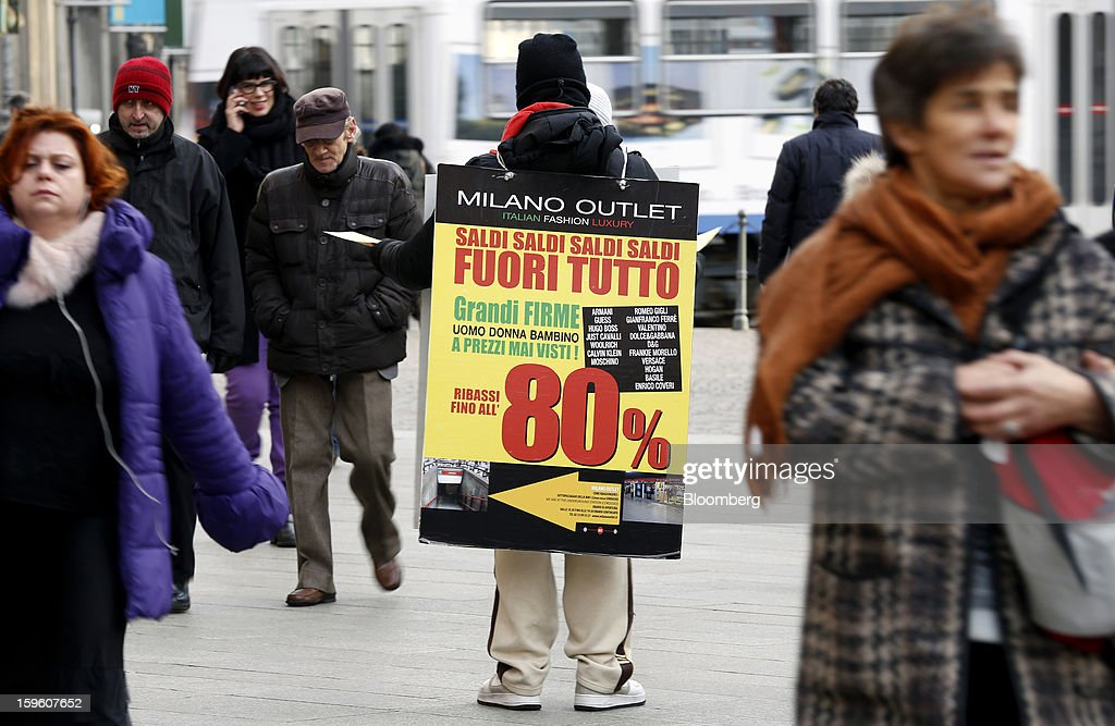 Pedestrians pass a man holding a banner advertising a sale in Milan, Italy, on Thursday, Jan. 17, 2013. The euro-area economy won't return to growth until the next quarter as a recovery in Italy is delayed and France continues to shrink, according to a survey of economists. Photographer: Alessia Pierdomenico/Bloomberg via Getty Images