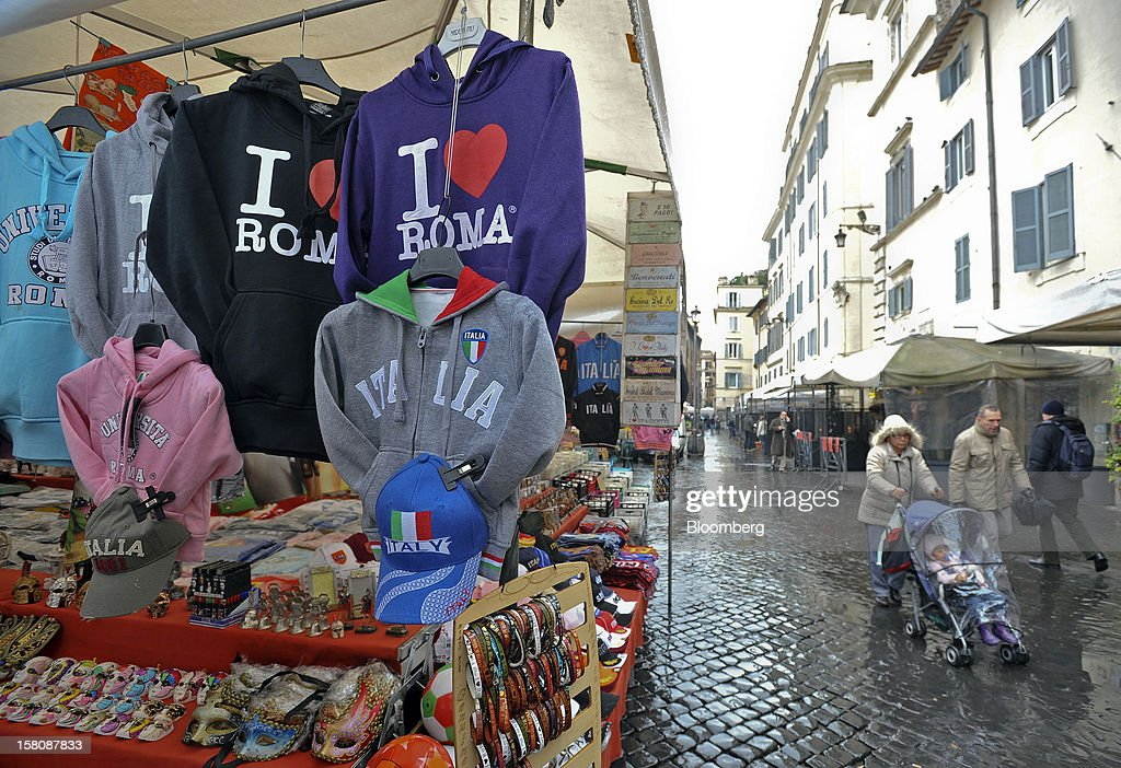 Pedestrians pass a market stall selling Italian-themed goods at the Campo dei Fiori market in Rome, Italy, on Monday, Dec. 10, 2012. The imminent end of Prime Minister Mario Monti's government fueled the largest increase in Italian borrowing costs in four months and threatened to open a new front in Europe's crisis fight before a year-end summit. Photographer: Victor Sokolowicz/Bloomberg via Getty Images