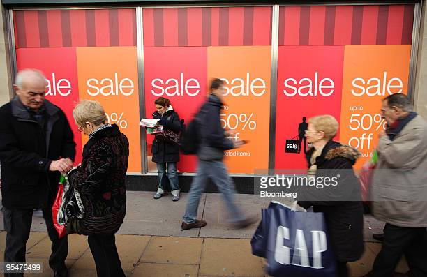 Pedestrians pass a Marks Spencer store advertising sales discounts on Oxford Street in London UK on Monday Dec 28 2009 More UK consumers stepped out...