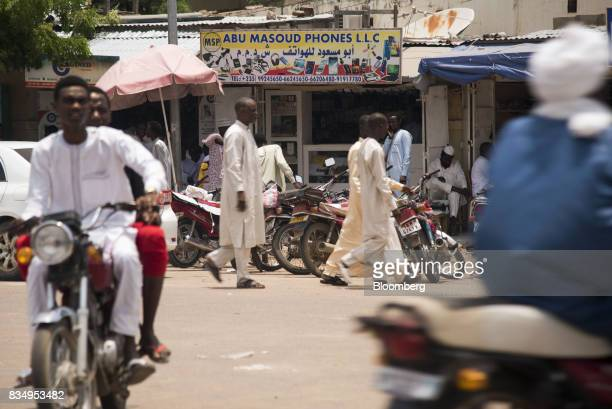 Pedestrians pass a mobile phone store in N'Djamena Chad on Wednesday Aug 16 2017 African Development Bank and nations signed agreement to finance a...