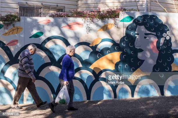 Pedestrians pass a mural painted on a boundary fence by artist Akisiew in Marrickville on August 7 2017 in Sydney Australia Perfect Match is an Inner...